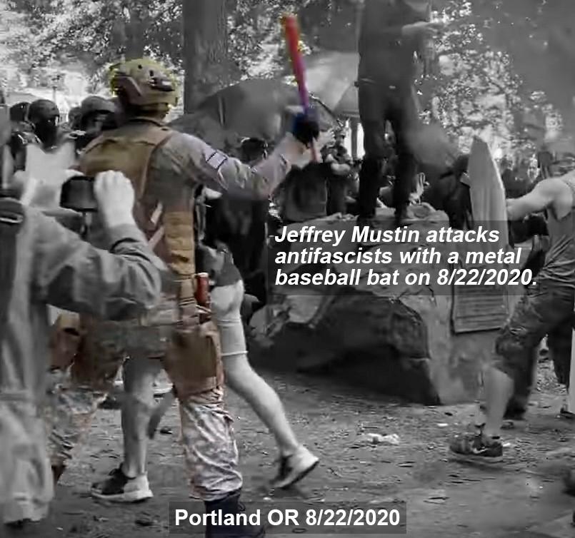 Jeffrey Mustin hits a counter demonstrator with a baseball bat